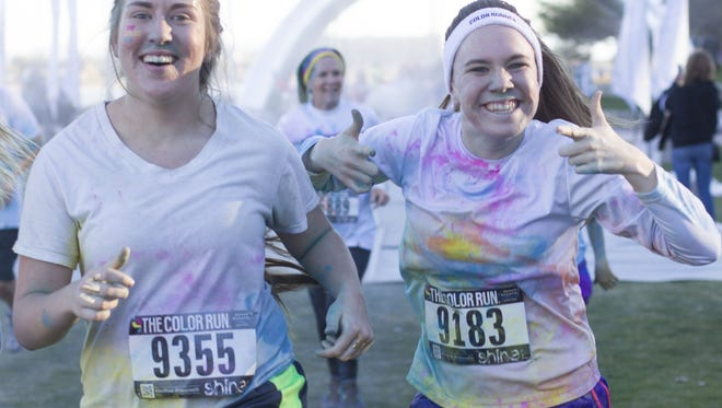 Runners celebrate after running through the glitter station and completing their tie-dye shirt during the Color Run 5k at Tempe Beach Park, Saturday, January 24th, 2015, in Tempe, Ariz.