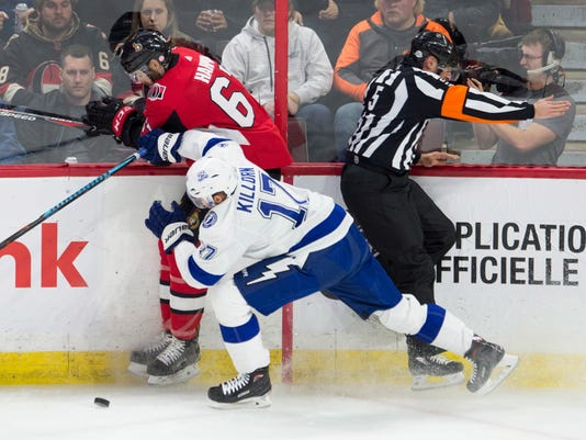 Referee Chris Rooney tries to avoid being checked by Tampa Bay Lightning left wing Alex Killorn and Ottawa Senators defenseman Ben Harpur during the first period of an NHL hockey game Thursday, Feb. 22, 2018, in Ottawa, Ontario. (Adrian Wyld/The Canadian Press via AP)