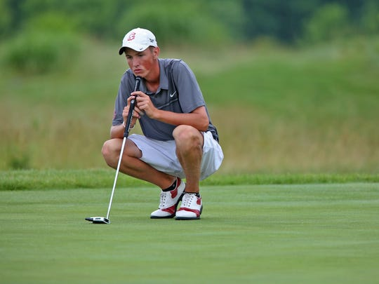 Center Grove's Noah Gillard waits to line up a putt