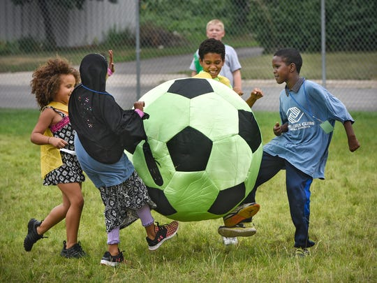A large soccer ball makes for an interesting game for children following a ceremony to announce a $50,000 grant from the Minnesota Super Bowl Host Committee to the Boys & Girls Clubs of Central Minnesota Tuesday, July 25, in St. Cloud.