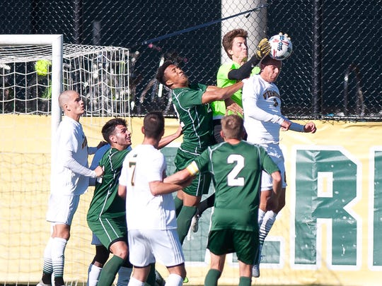 Vermont goalkeeper Aron Runarsson, center, jumps to catch a ball over the head of teammate Arnar Steinn Hansson during Saturday's men's soccer game at Virtue Field.