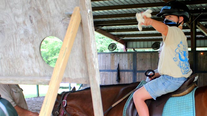 Liam Watson tosses a plush toy toward a target hole in a Pegasus relay activity during their therapeutic riding session.