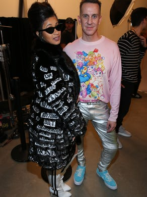 Cardi B and designer Jeremy Scott pose backstage at