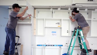 Travis Hillesland, left, and Jackson Birdwell, right, of ModerNash install IKEA cabinetry in a kitchen at the Fifth and Main Building June 16, 2017.
