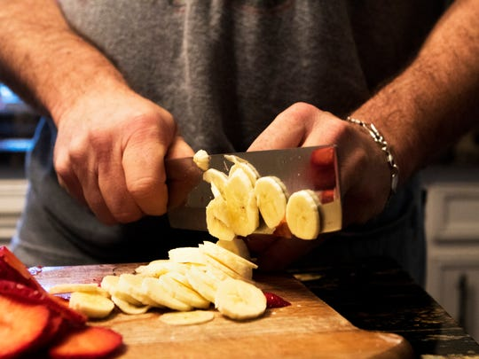 Mark Phelps slices a banana while he makes breakfast