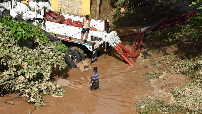 Work crews pump out muddy water from the streets of Cihuatlan along the Rio Marabasco on Saturday, October 24, 2015. Hurricane Patricia slammed into Mexico's southwest Pacific Coast causing flooding and mudslides but the area has spared the extensive damage that was predicted.