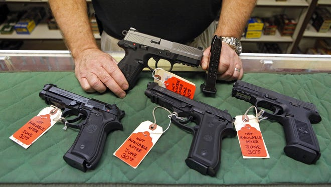 In this 2013 photo, Richard Taylor manager of Firing-Line gun store in Aurora, Colo., shows some of the pistols he wouldn't be able to sell after a law was enacted limiting the size of ammunition magazines.
