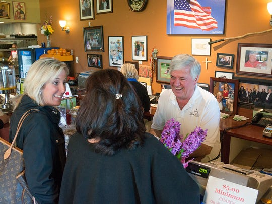 Working the counter, George Dimolpoulos greets customers Laurie Transou, of Northville, and Anne Lamacchia, of Livonia.