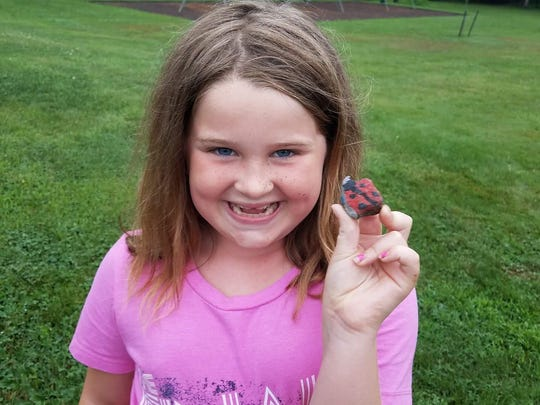 """Riley Gildea, 7, of Manville shows off one of the rock creations. Playing hide-and-seek with hand-painted rocks has become this summer's """"big thing."""" Community group members decorate and hide rocks around towns — in safe, public spots — for others to find and rehide."""