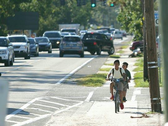 School children ride their bikes on Terry Street in