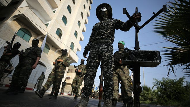 Fighters from Ezz-Al Din Al Qassam Brigades, the armed wing of Palestinian Hamas movement attend a protest against the security measures at the al-Aqsa mosque after Friday prayers in Gaza City on July 25, 2017.