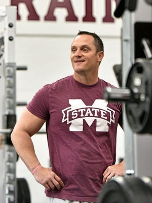 Mississippi State's new baseball coach Andy Cannizarro talks with trainers between sets of an early morning workout at Mississippi State.