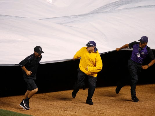 Field guards join a member of the grounds crew to pull the tarpaulin on the diamond of Coors Field as heavy rain halts play after the Colorado Rockies were retired by the Atlanta Braves in the second inning of a baseball game Saturday, July 23, 2016 in Denver. (AP Photo/David Zalubowski)