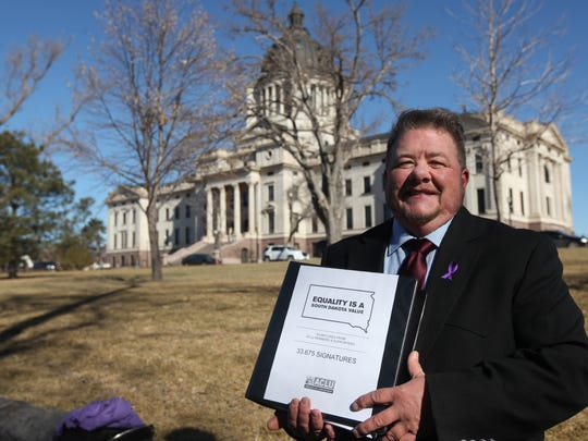 Terri Bruce holds a binder full of signatures before delivering to Gov. Daugaard's office with other ACLU members and supporters at the South Dakota State Capitol in Pierre on Tuesday, Feb. 23, 2016.