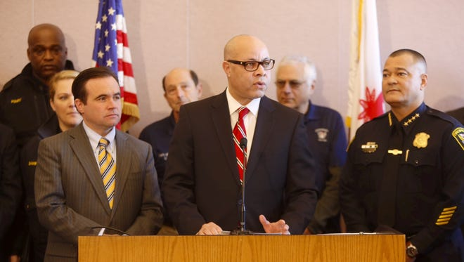 City Manager Harry Black, center, discusses reduced violent-crime rates at a press conference with Mayor John Cranley, left, and Police Chief Jeffrey Blackwell, right, Tuesday, Jan 13, 2015.