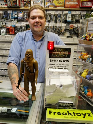 Freaktoyz's Matthew Rieley poses with a Star Wars figure Tuesday December 1, 2015 at his store in Sheboygan.  Rieley bought a entire block of tickets to the showing of Star Wars later this month and is raffling off tickets.