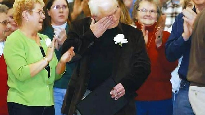 Former Prattsburgh basketball coach Jim Burke is overcome with emotion after the unveiling of the new Burke Gymnasium sign at a game Jan. 29, 2011.