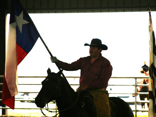 A cowboy holds the Texas flag during the opening ceremony of the team roping event during the annual Ranch Hand Breakfast at the King Ranch.