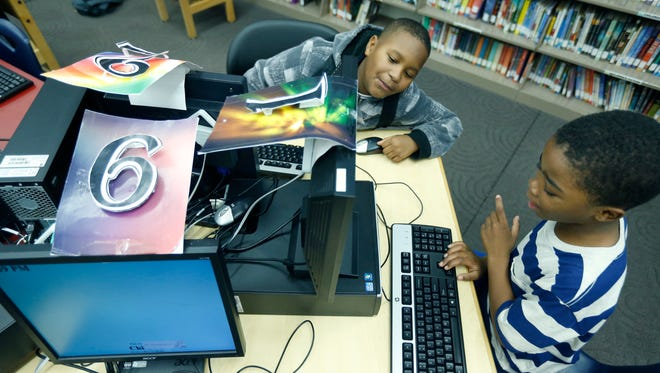 School No. 33 students Zavian Curry, 9, and Kameron Haskell, 8, use the computers at the Sully Public Library. Students have to read for at least 15 minutes before being allowed to access computers.