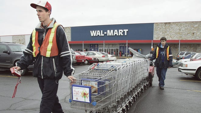 Wal-Mart employees collect shopping carts.