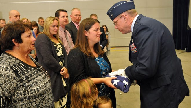 Nevada Adjutant General, Brig. Gen. Bill Burks presents Joey Ernst, the sister of Nevada Guard Tech. Sgt. Stephanie McLaughlin, with a folded flag during a memorial service at the Nevada Air National Guard Base in Reno on Saturday. McLaughlin, Burks' executive aide since 2010, died of a stroke Sept. 25.