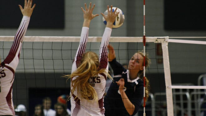 Allyson Severance of North Branch gets a kill shot past Buchanan's Megan Adkerson on Thursday at Kellogg Arena. Severance and Olivia Fike led the Broncos with 14 kills each.
