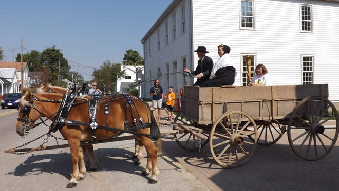 Janice McGuire holds the Indiana bicentennial torch on Sept. 25 as Chris and Lisa Allen transport her in a wagon. The torch's journey through Wayne County began from the Levi Coffin House in Fountain City. The wagon is passing by the home's interpretive center, which is nearly complete.