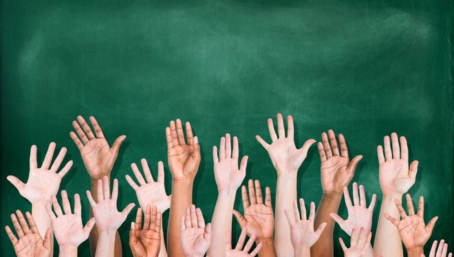 Students raise their hands in front of a blackboard.