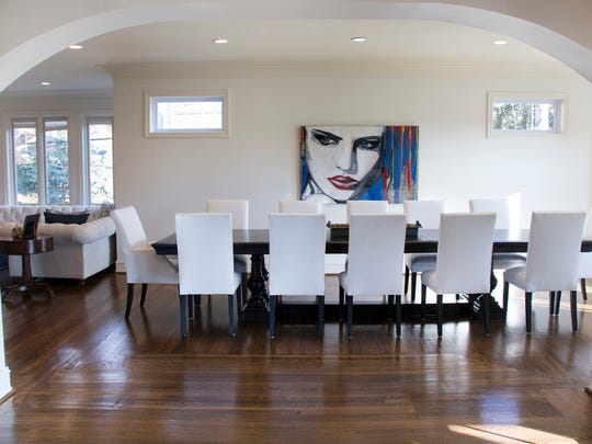 Dining for 12 in the space that used to be the Victorian parlor. Walls were removed and doors opened into wide arches to make the main floor a streamlined, snow-white canvas for dramatic at.