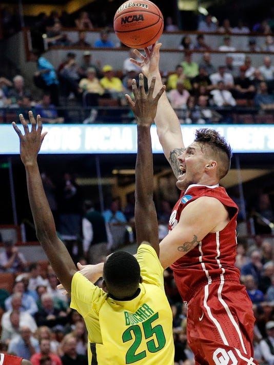 Oklahoma forward Ryan Spangler, right, shots over Oregon forward Chris Boucher during the first half of an NCAA college basketball game in the regional finals of the NCAA Tournament, Saturday, March 26, 2016, in Anaheim, Calif. (AP Photo/Gregory Bull)