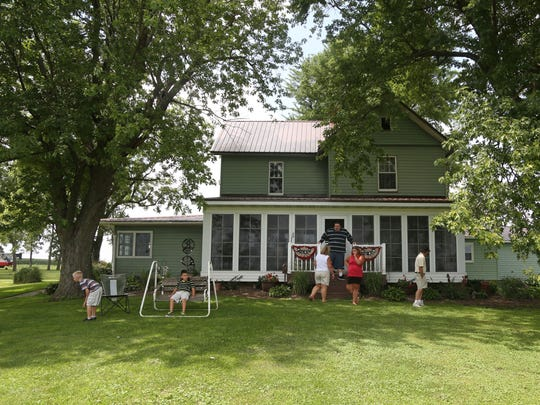 The Bennett family, Andrea, Christopher, Gina, Kelly, Jake Morris and Owen Morris gather outside of Gina and Kelly's home which has been in Gina's family for six generations on Wednesday, Aug. 3, 2016, in rural Keota.
