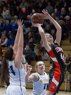 Cedarburg sophomore Abby Belschner (right) goes to the basket defended by Germantown seniors Kenzie Schmitz (34) and Taylor Weitermann (11) in a North Shore Conference game on Jan. 6. The Warhawks won, 59-45.