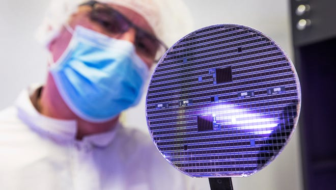Steven Young, BE Lab manager and process/equipment engineer for Soitec Phoenix Labs, shows off a concentrator solar cell at the facility, Tuesday, January 6, 2015.