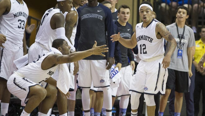 Monmouth Hawks guard Justin Robinson (12) celebrates with teammates during the second half of an NCAA college basketball game Thursday, Nov. 26, 2015, in Orlando, Fla. Monmouth won 70-68(AP Photo/Willie J. Allen Jr.)
