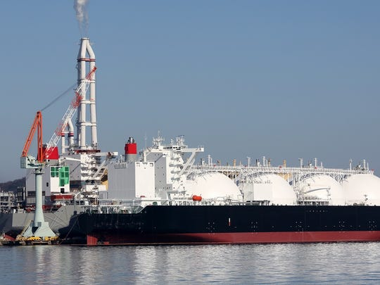 Liquefied natural gas is loaded onto a shipping vessel with insulated tanks.