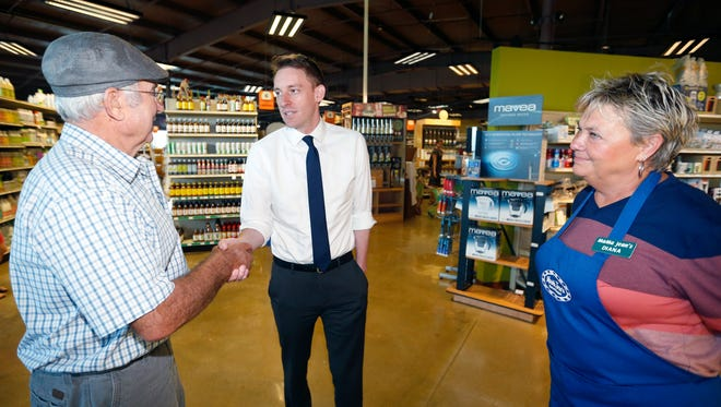 Fred Rust, from Edgar Springs, Mo., shakes hands with Missouri Secretary of State Jason Kander during a visit to MaMa Jean's Natural Market as MaMa Jean's co-owner Diana Hicks stands nearby on Tuesday, July 19, 2016.