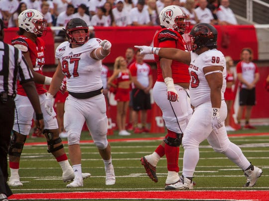 Defensive linemen Robert Torgerson (left) and Anu Poleo (right) celebrate after a play during the T-Birds' 24-0 loss at Utah, Thursday, Sept. 1, 2016.