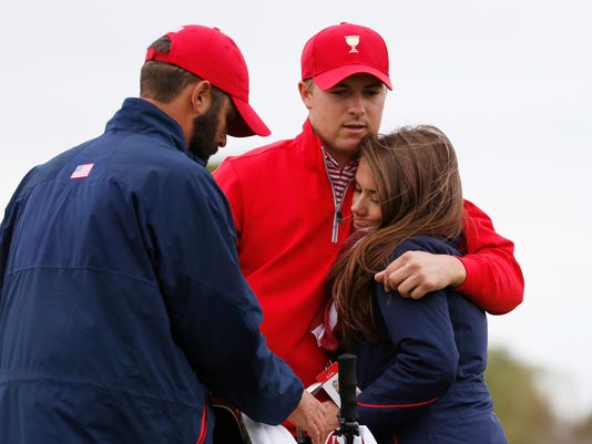 FILE - In this Oct. 11, 2015, file photo, United States' Jordan Spieth, center, is embraced by his girlfriend Annie Verret following his loss to International team player Marc Leishman of Australia in their singles match as Dustin Johnson, left, watches at the Presidents Cup golf tournament at the Jack Nicklaus Golf Club Korea, in Incheon, South Korea. Spieth is out of the Olympics. International Golf Federation president Peter Dawson announced the decision at the British Open. Spieth had been strongly debating whether to go over the last three days before reaching his decision on Monday, July 11, 2016. He will be replaced by Matt Kuchar. (AP Photo/Lee Jin-man, File)