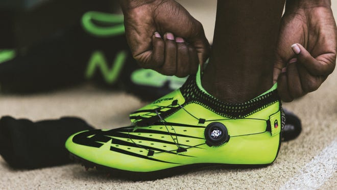 This undated photo provided by New Balance shows U.S. sprinter Trayvon Bromell adjusting his shoes.