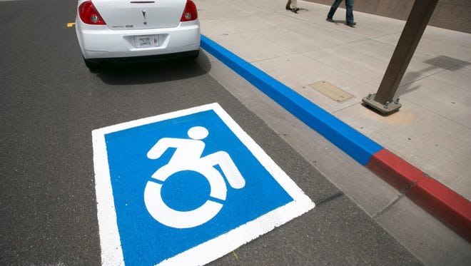 Phoenix's new accessibility icon is seen painted in a parking spot at Third Avenue and Adams Street in downtown Phoenix. Existing signs will be replaced with the new icon as need arises.