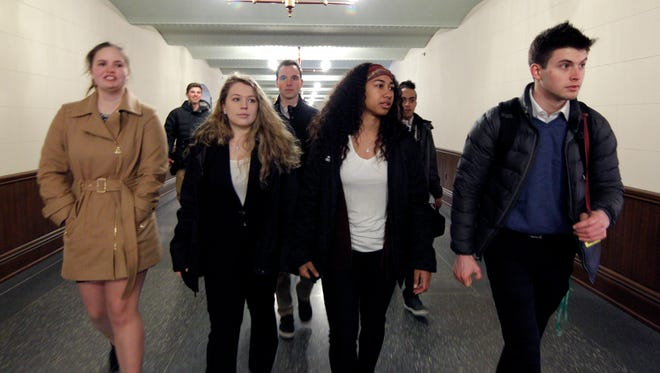 Kalamazoo Central High School students Jenna Bowker, center left, and Talia Edmonds, center right, walk through the state Capitol after meeting with Sen. Morris Hood III, D-Detroit, in his office, Thursday, Feb. 22, 2018, in Lansing, Mich.
