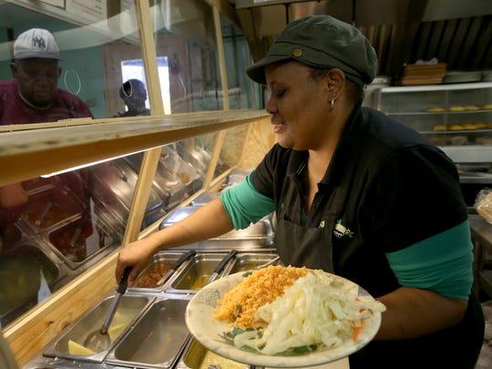 Suzett Williams fills lunch orders at Livie's Jamaican Restaurant on Chili Avenue.