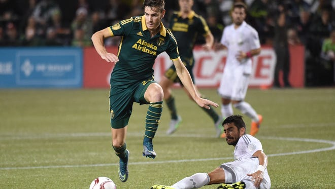 Portland Timbers midfielder Lucas Melano (26) leaps over Sporting KC midfielder Paulo Nagamura (6) during the first half of a knockout round MLS playoff soccer match in Portland, Ore. on Thursday, Oct. 29, 2015.