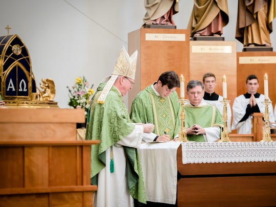 Rev. Cory Mayer signs documents on his formal installation as pastor of the newly-created Ave Maria Parish, flanked by Bishop Frank Dewane, left, and Deacon John Jarvis.