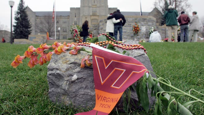 People embrace as they look at a memorial for the shooting victims at Drillfield on the campus of Virginia Tech in Blacksburg, Va., in 2007.