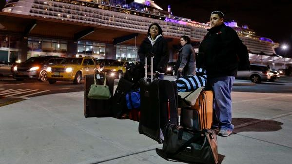Passengers from the Royal Caribbean cruise ship, Anthem of the Seas, await transportation after arriving at Cape Liberty cruise port, Wednesday, Feb. 10, 2016, in Bayonne, N.J. Carrying 4,500 passengers and 1,600 crew members, the ship returned early from a seven-day cruise to the Bahamas after it was battered by a major storm in the Atlantic Ocean. (AP Photo/Julie Jacobson)