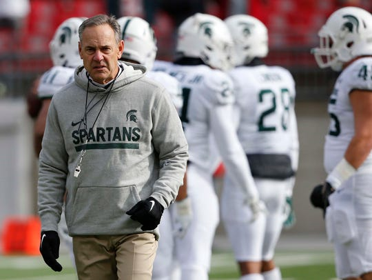 Michigan State coach Mark Dantonio enters the field