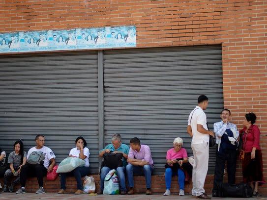 People wait to board a bus in Caracas, Venezuela, on