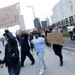 Protestors, some with arms and hands raised, march toward the Tulsa County Sheriff's office in Tulsa, Oklahoma, April 14. They rallied calling for the firing of a sheriff's deputy who can be heard in a video cursing at suspect Eric Harris as he was dying in a recent Tulsa police shooting.