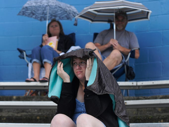 Lee Ralston shelters from the rain underneath her jacket before the Staunton Braves game against the Aldie Senators was postponed because of inclement weather in Staunton on Friday, June 20, 2014. The game has been tentatively rescheduled to June 30.